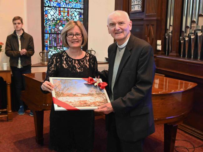 Gill Watson presents Mr Scott with a painting featuring Preston Mill at a reception at Prestonkirk Parish Church in East Linton. Image Garry Menzies
