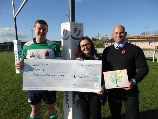 Greg Patrizio, club captain at Dunbar RFC, and Justin Pearce, president of the club, hand over a cheque to Sara Fitzsimmons, chief executive officer of SiMBA
