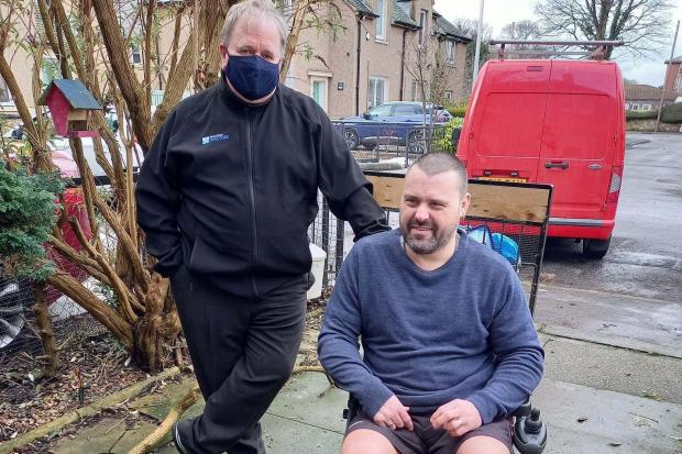 Robert Moffat who has MS tries out his electric wheelchair which was presented by Davie Martin of Radio Saltire