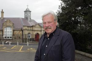 Community councillor Roy Baines beside the newly restored clock at Ormiston Primary School