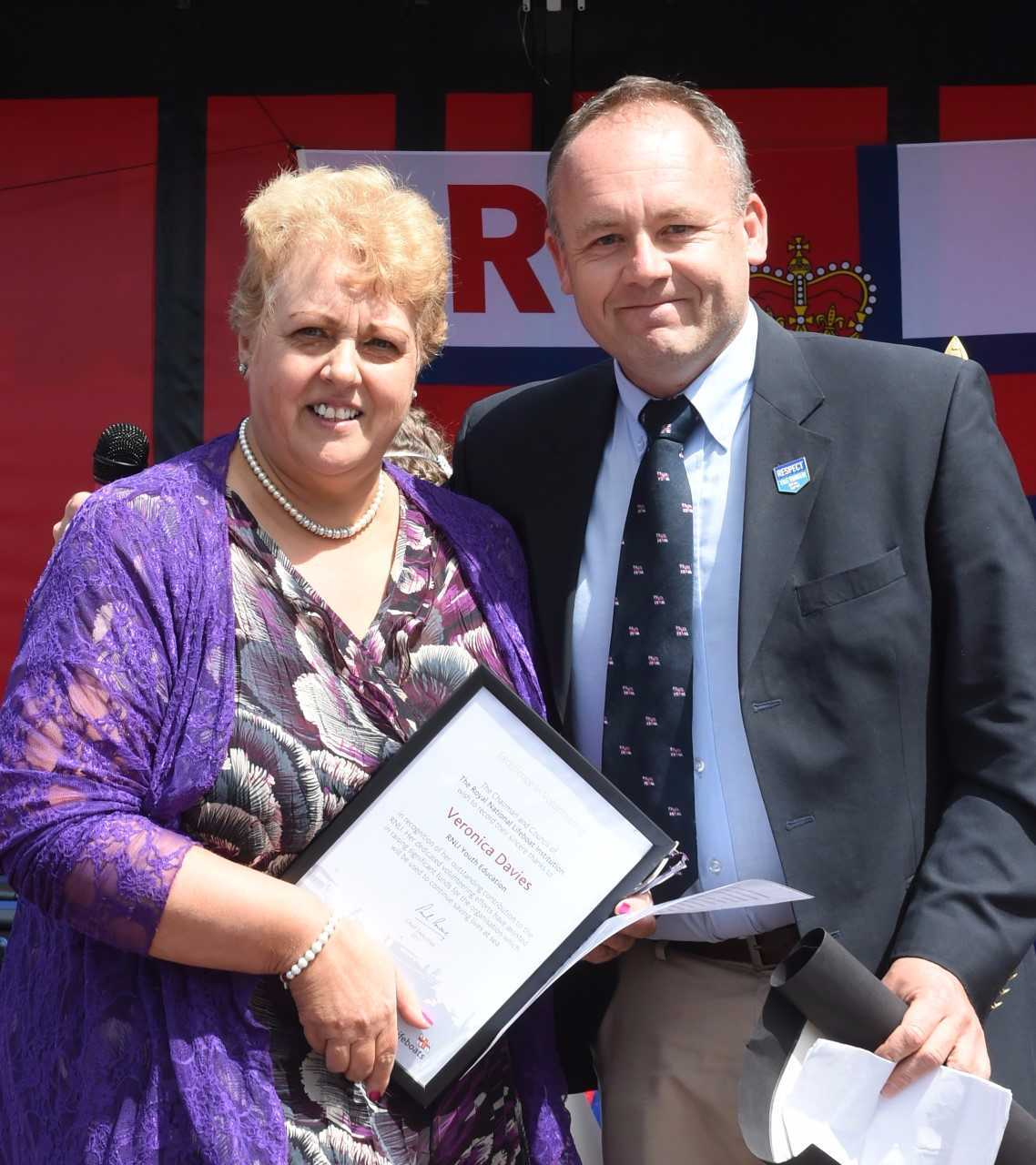 Mark Lees, Dunbar RNLI Station chairman, presents a special certificate to Veronica Davies