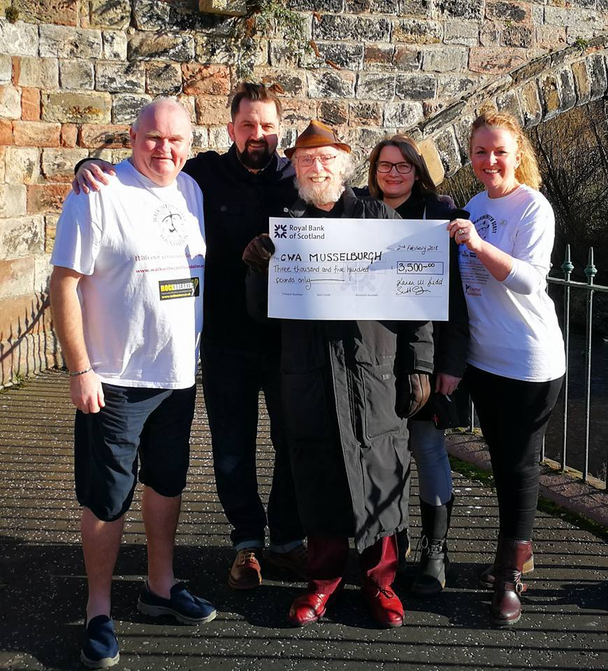 Actor James Martin, who plays the character Eric in the TV comedy series Still Game, centre, is presented with the cheque for £3,500 from the Walk With Scott Foundation last Friday. A Musselburgh resident and strong supporter of the Hollies Day Centre, h