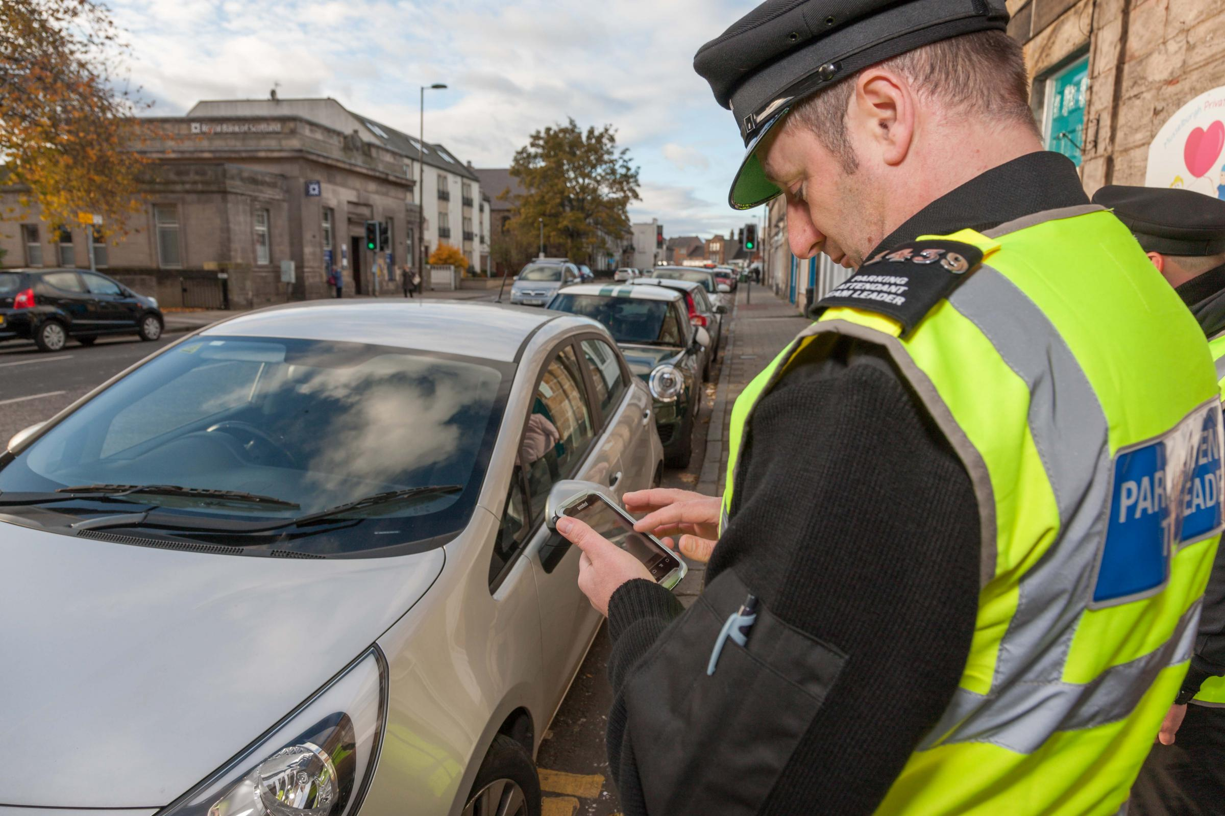 A parking attendant on patrol in Musselburgh. The council is now putting proposals to charge for parking in town centres out to public consultation
