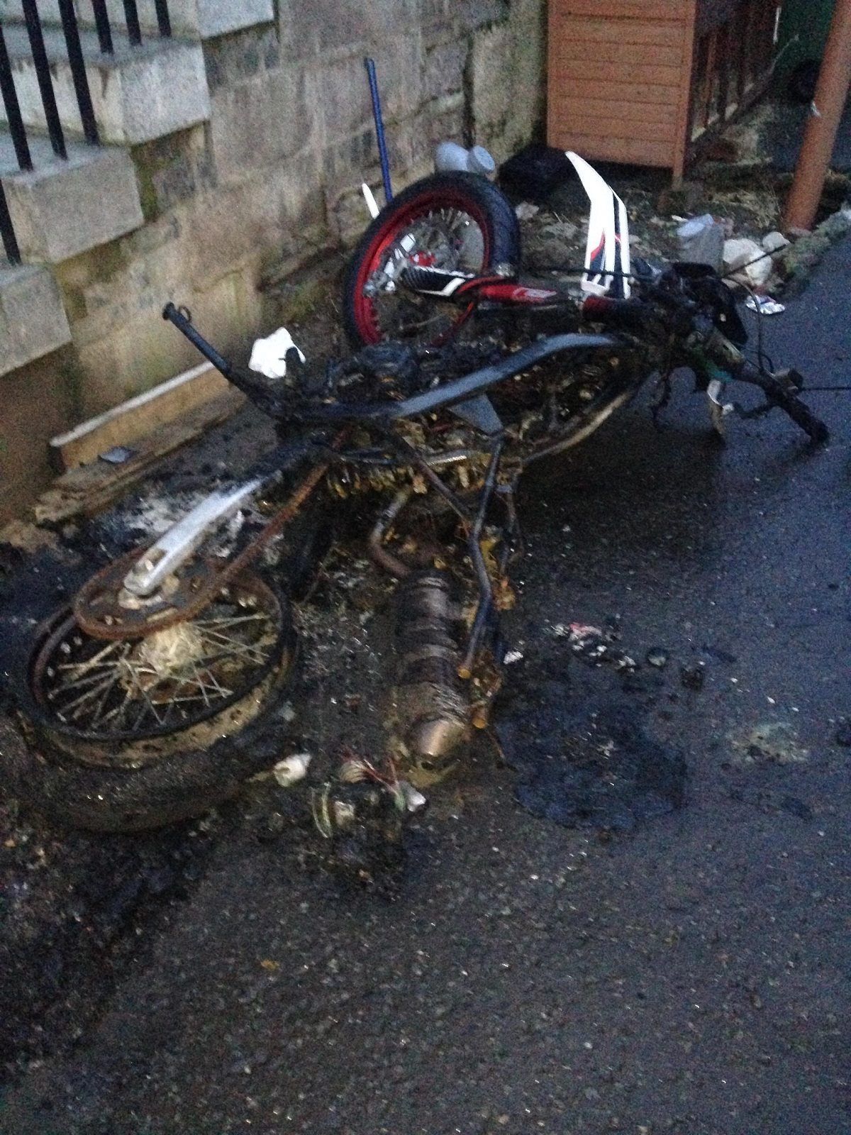 The badly damaged bike lies charred just a few feet from the pet enclosure