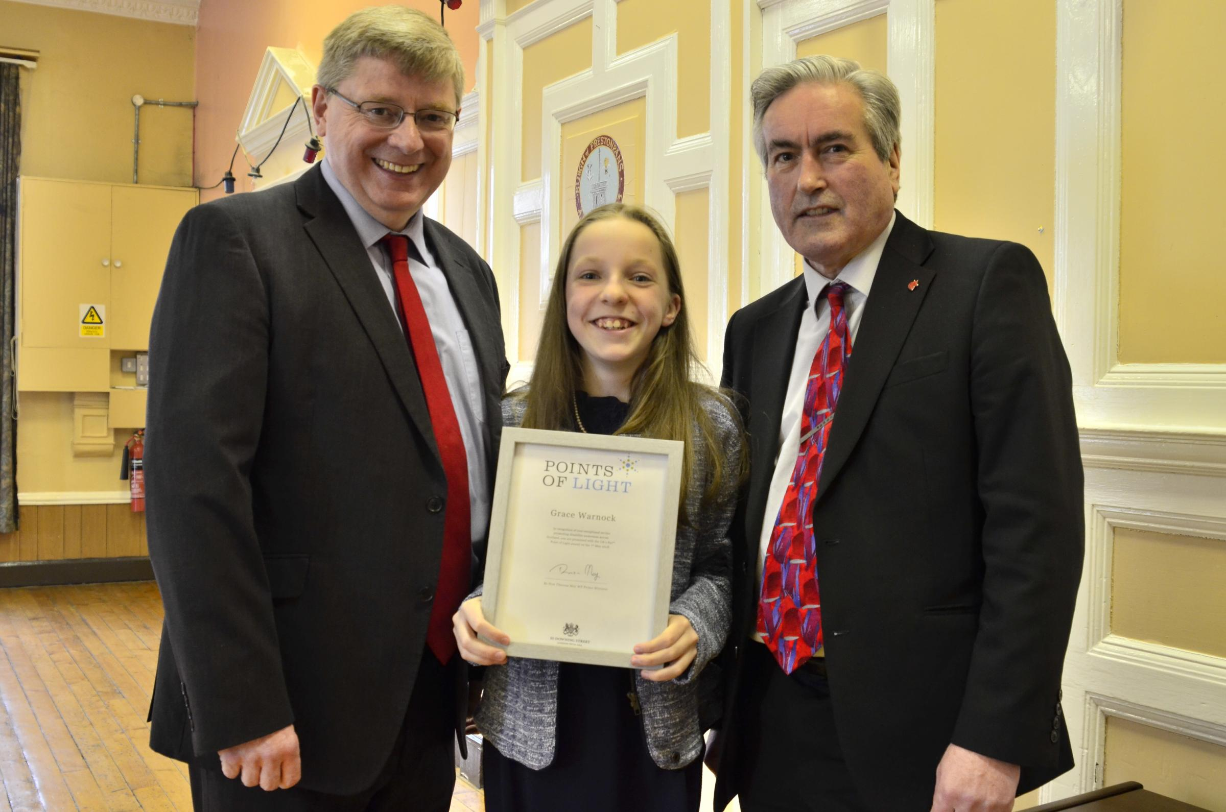 Grace Warnock receives her Points of Light award from Iain Gray and Martin Whitfield