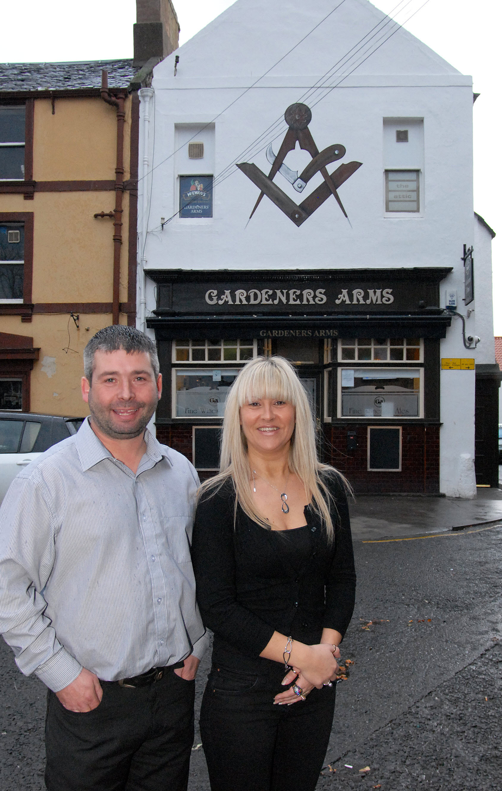 Michael and Wendy Peters outside the Gardeners Arms in 2011. Part of the former The Pheasant pub (now Jo's Kitchen), can be seen on the left of the image